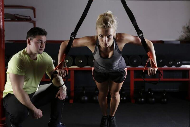 a woman working out in a gym with an instructor