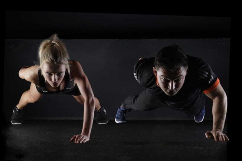 man and woman doing press ups