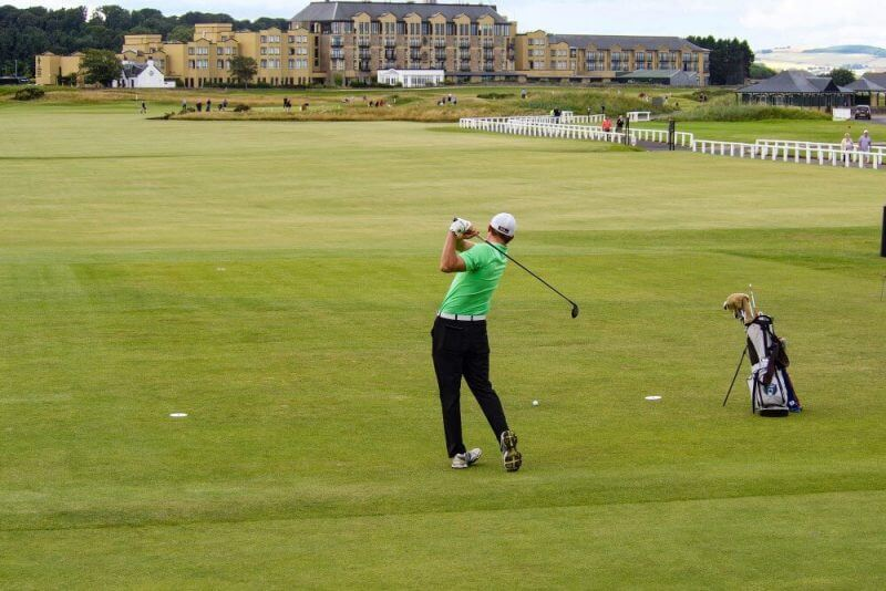 a man playing gold in a large golf field