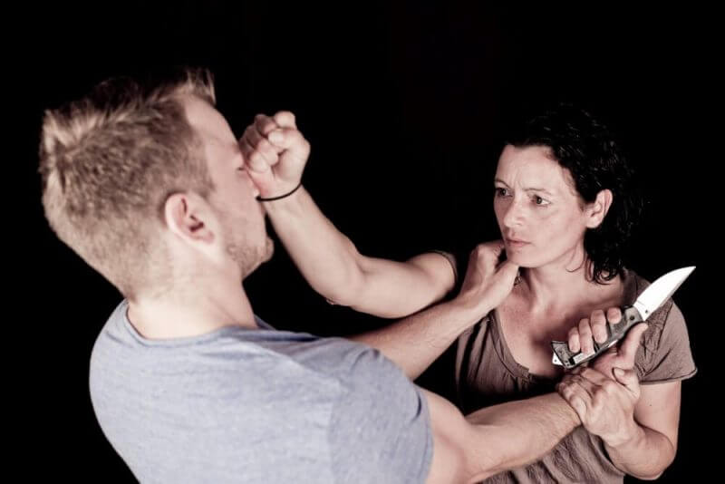 a man holding a knife at a woman