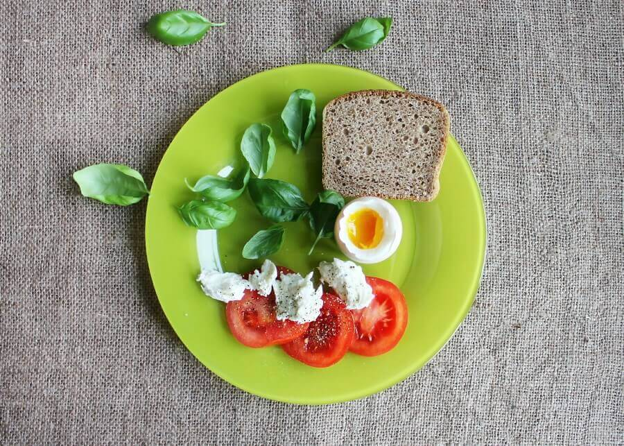 slice of bread,vegetables,egg and tomatoes on a green plate