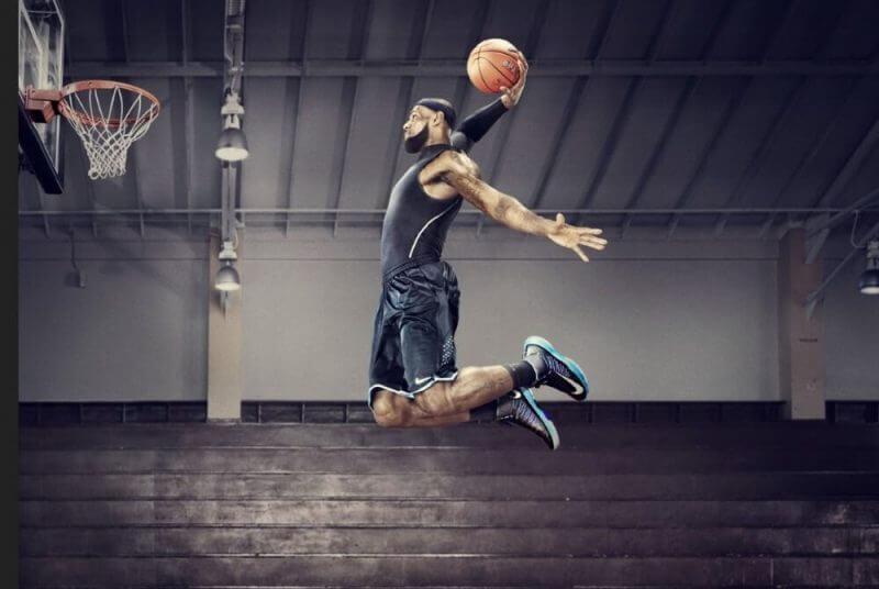 a man jumping to dunk a basketball