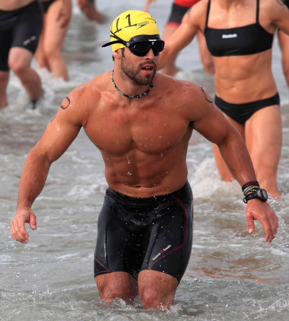 Rich Froning strategically walks backward into the water while wearing swimming fins during the 2012 Reebok CrossFit Games at Camp Pendletons San Onofre Beach, Jul. 12. CrossFit athletes competed in a true test of fitness that included swimming 700-meters in the Pacific Ocean, biking 6-miles through grueling terrain, running up more than 1400 vertical feet and ending the days events by maneuvering their way though a Marine Corps Obstacle Course.
