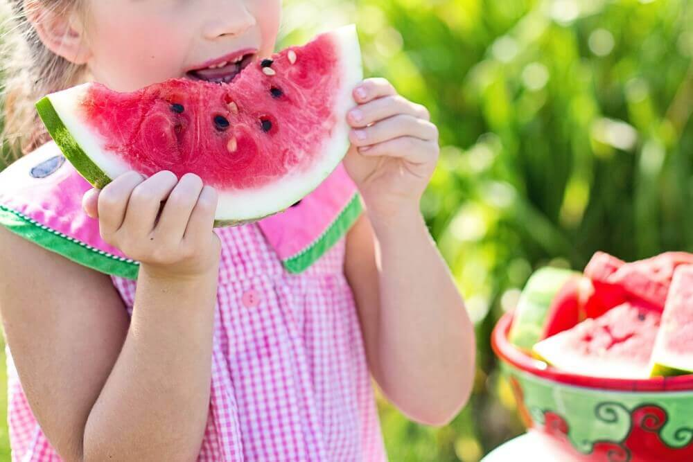 a young girl eating a piece of watermelon