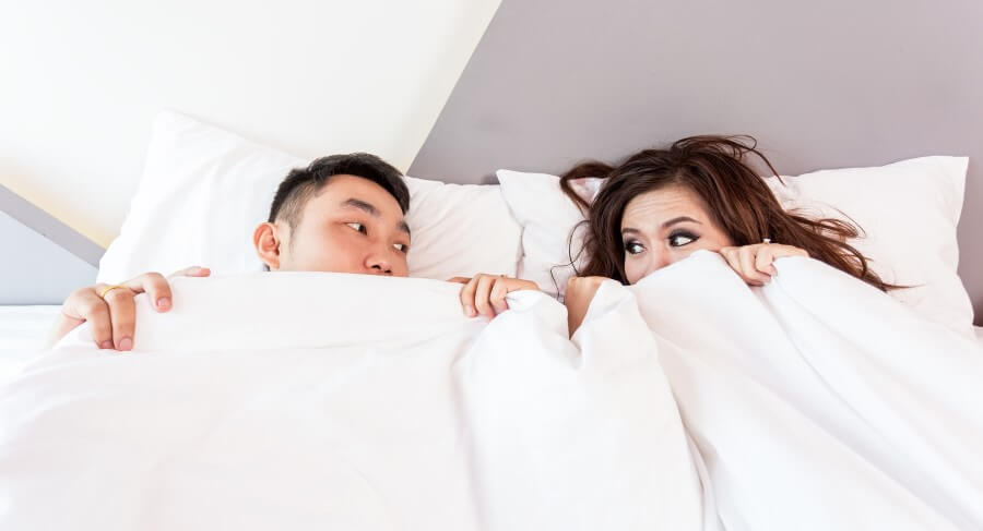 man and woman covering themselves with white sheets in a bed
