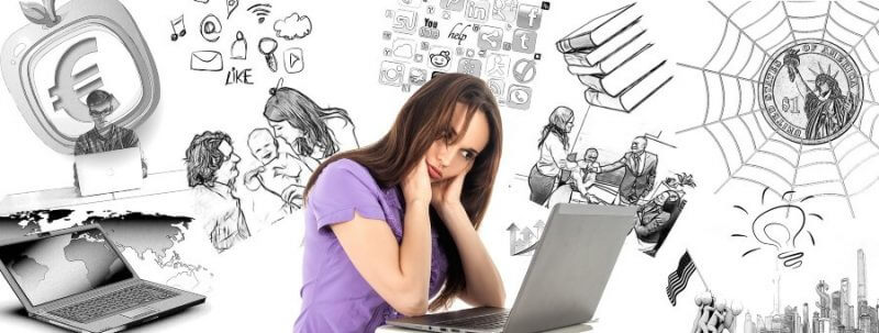 lady holding her head in front of a laptop and many drawings in the background