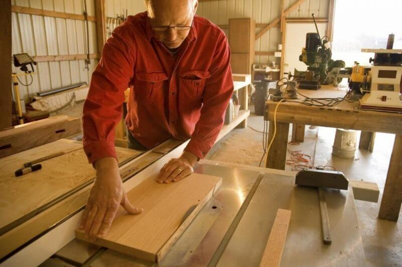 man working on wood designs