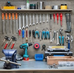 Ultimate Small Shop module one represented by tools placed on a wall