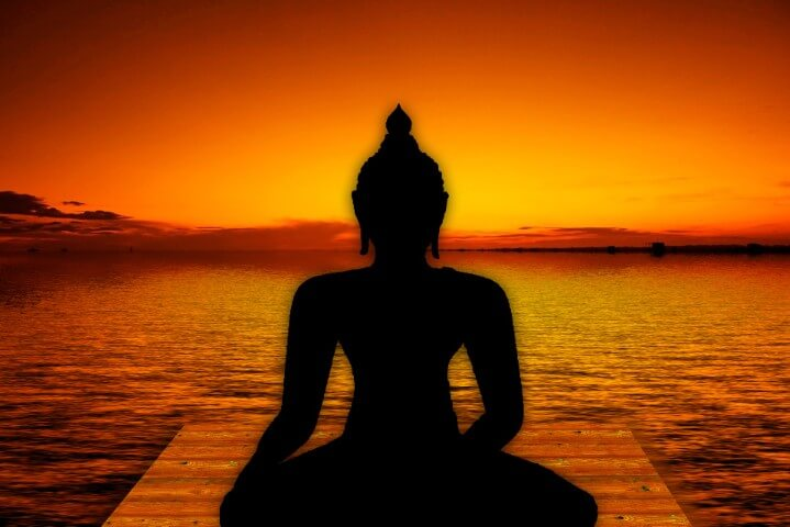 The Wealth Activation Blueprint yoga buddha figure with a lake on the background of a sunset